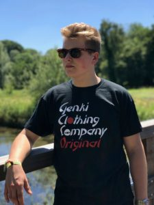 Teenage boy standing on a bridge wearing a black t-shirt with the Genki Clothing Company Original logo on the chest area