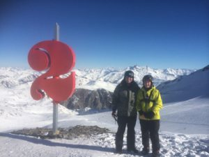 A dad and his son standing at the top of a snowy mountain next to a large number 2