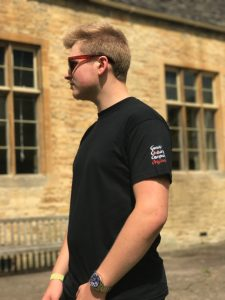 Teenage boy wearing a black t-shirt standing in front of a building