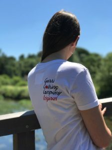 A teenage girl on a bridge looking away from the camera wearing a white t-shirt with the Genki Clothing Company Original logo on the rear shoulder