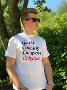 Teenage boy standing by a tree wearing a white t-shirt with the Genki Clothing Company Original logo