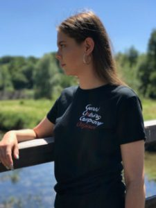 Teenage girl standing on a bridge in the countryside wearing a black t-shirt with Genki Clothing Company Original logo