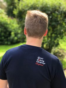 Teenage boy wearing dark blue t-shirt with logo on the shoulder blade