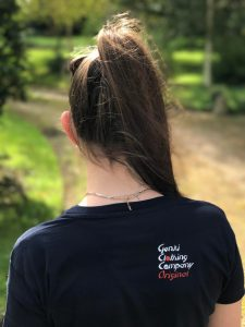 Teenage girl wearing dark blue t-shirt with logo on the shoulder blade