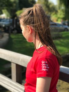Teenage girl wearing red t-shirt with logo on the sleeve
