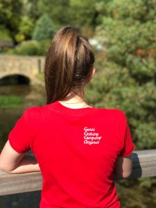 Teenage girl wearing red t-shirt with logo on the shoulder blade