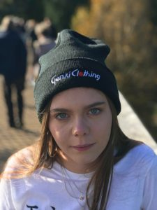 Woman wearing a black beanie with the words Genki Clothing