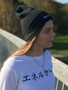 Woman wearing a white t-shirt with the Japanese word for Genki and a black beanie