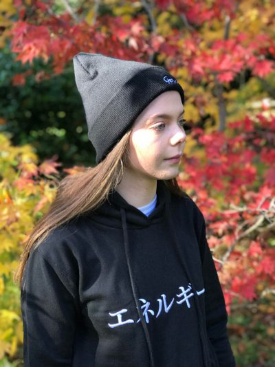Woman wearing a black hoodie with the Japanese word for Energy and a black beanie