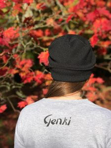 Back of a woman wearing a grey t-shirt with the word Genki on the top and a black beanie