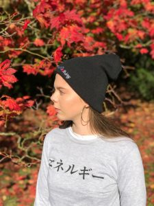 Woman wearing a black beanie and a white t-shirt featuring the Japanese word for Energy