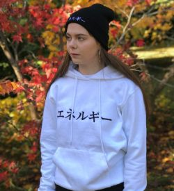Woman wearing white hoodie with Japanese word for Energy and a black beanie