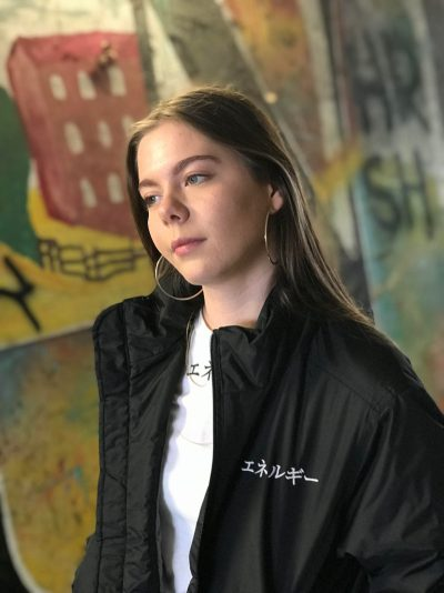 "Teenage girl wearing a black bomber jacket and a white t-shirt with the word ""Energy"" in Japanese"