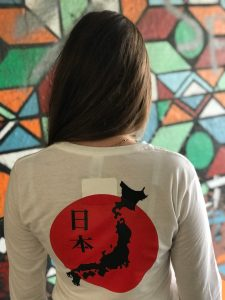 Back of a teenage girl wearing a white t-shirt featuring the map of Japan against the Japanese flag
