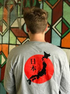Back of a teenage boy wearing a grey t-shirt featuring the map of Japan against the Japanese flag