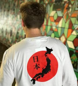 Back of a teenage boy wearing a white t-shirt featuring the map of Japan against the Japanese flag