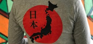 Close up photo of the back of a grey t-shirt with the design of the map of Japan against the red flag of Japan