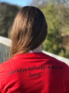 The back of a teenage girl wearing a red genkiclothing.co.uk t-shirt with the word Love