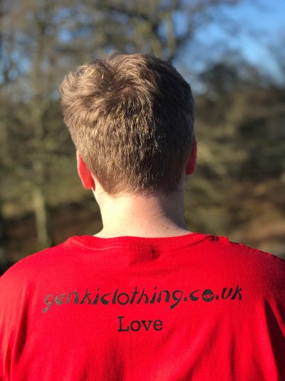 The back of a teenage boy wearing a red genkiclothing.co.uk t-shirt with the word Love