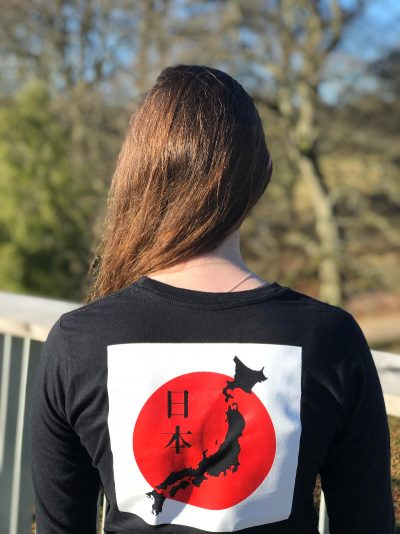 Back of a teenage girl wearing a black t-shirt featuring the map of Japan against the Japanese flag