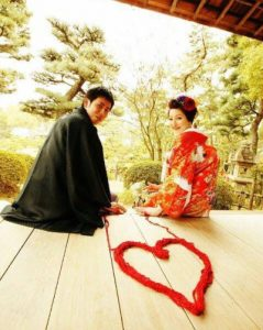 A Japanese man and woman sitting next to a heart made of wool on the floor next to them