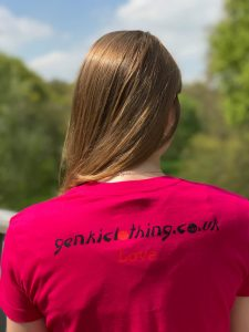 Back of a teenage girl wearing a dark pink t-shirt featuring the word Love