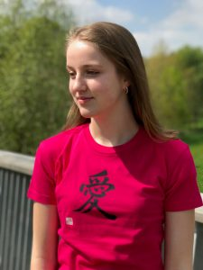 Teenage girl wearing a dark pink t-shirt featuring the kanji character for Love