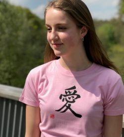 Teenage girl wearing a pink t-shirt featuring the kanji character for Love