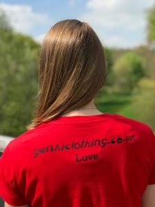 Back of a teenage girl wearing a red t-shirt featuring the word Love