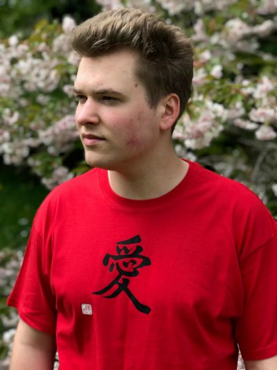 Teenage boy wearing a red t-shirt featuring the kanji character for Love