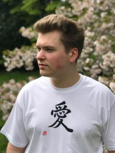 Teenage boy wearing a white t-shirt featuring the kanji character for Love