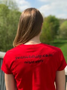 Back of a teenage girl wearing a red t-shirt with the words ninja cats