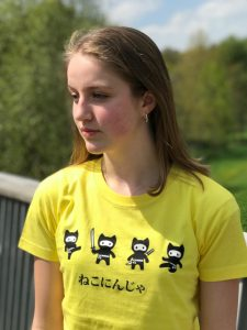 Teenage girl wearing a yellow t-shirt featuring ninja cats