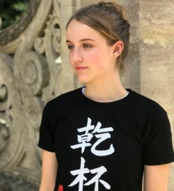 Teenage girl wearing a black t-shirt featuring the word Cheers in kanji