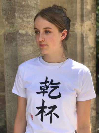Teenage girl wearing a white t-shirt featuring the word Cheers in kanji