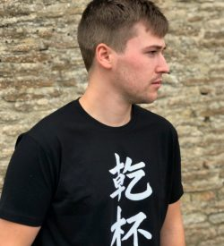 Teenage boy wearing a black t-shirt featuring the word Cheers in kanji