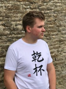 Teenage boy wearing a white t-shirt featuring the word Cheers in kanji